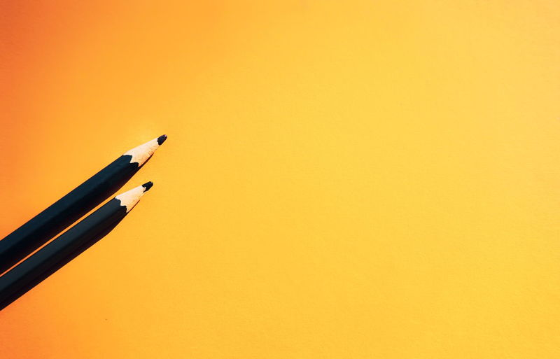 Writing Instrument Copy Space Pen Indoors  Yellow Colored Background Orange Color Studio Shot No People Close-up Single Object Black Color Still Life Simplicity Yellow Background Pencil Fountain Pen High Angle View Office Minimalism Modern