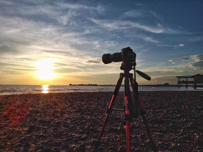Sky Photography Themes Tripod Sunset Camera - Photographic Equipment Outdoors Cloud - Sky No People Technology Lens - Eye Telescope Nature Astronomy Sunbeam Sunshine Sunlight Sunset Silhouettes Sunset_collection Nature Standing Water Scenics Tranquility Beach Sand