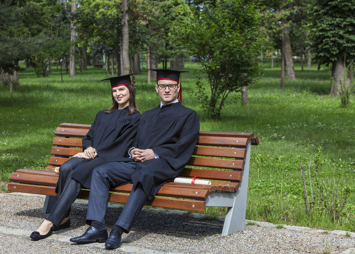 Portrait of a couple in the graduation day sitting on a bench in a park. Graduation Couple Woman Young Man Happy Park Beautiful Portrait People Girl Smile Cheerful Success Joy Education Two School Hat Student Cap College University Achievement Gown Graduate Degree Adult Successful Outdoor Students Friendship Uniform Bench Sit Together Rest Summer Colleagues Sitting Two People Looking At Camera Emotion Clothing Young Adult Togetherness Park Bench Couple - Relationship Happiness Outdoors
