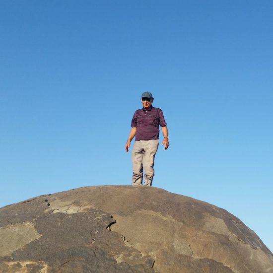 Low angle view of man in sunglasses standing on rock against clear blue sky