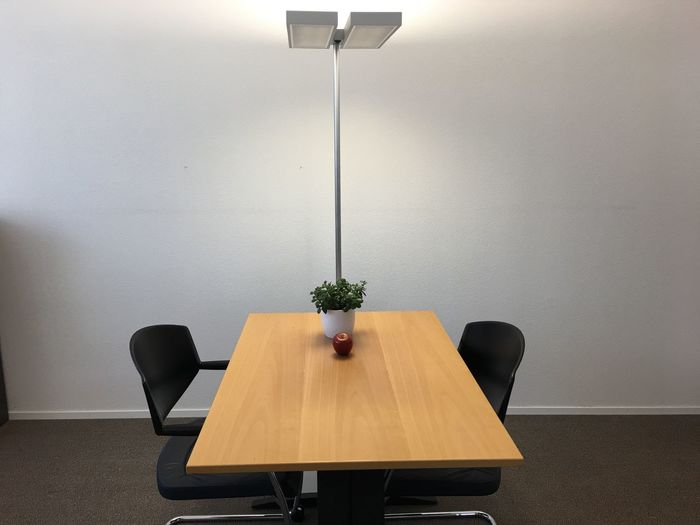 Empty chairs and table by wall in office
