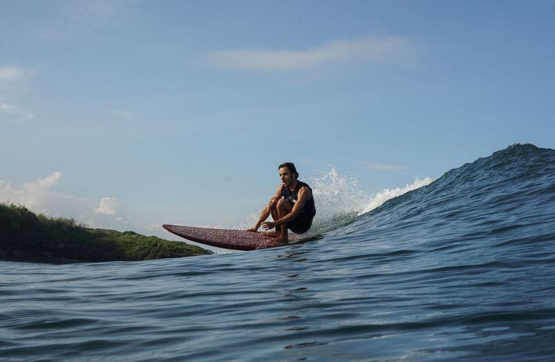 Man sitting on surfboard in sea against sky