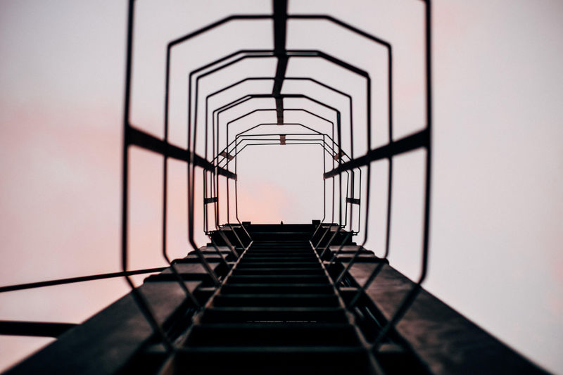 Directly Below Shot Of Metallic Ladder Against Sky During Sunset