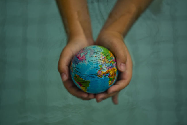 Above close up looking down on hands holding the world over water Atlantic Ocean Hand Holding Hands Map Plant Power Africa America Cat Citizen Of The World Citizenship Continent Ecology Energy Ethnic Europe Ocean Planet Protection Refugees Sustainability Sustainable Sustainable Resources Water World