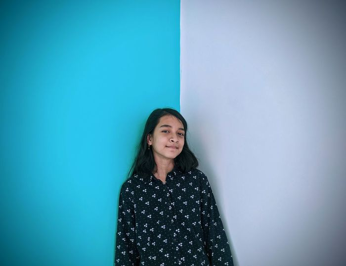 Portrait of smiling young woman standing against 2 color's wall