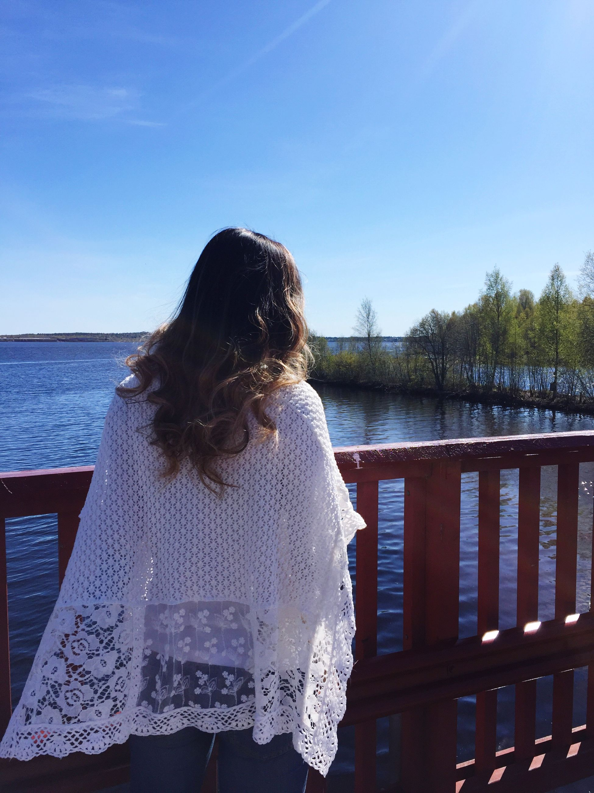 water, sea, rear view, leisure activity, lifestyles, railing, blue, sky, sunlight, person, clear sky, horizon over water, day, nature, standing, headshot, long hair, waist up