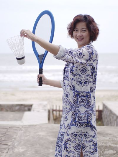 Portrait Of Smiling Woman Playing Badminton Against Sea And Sky
