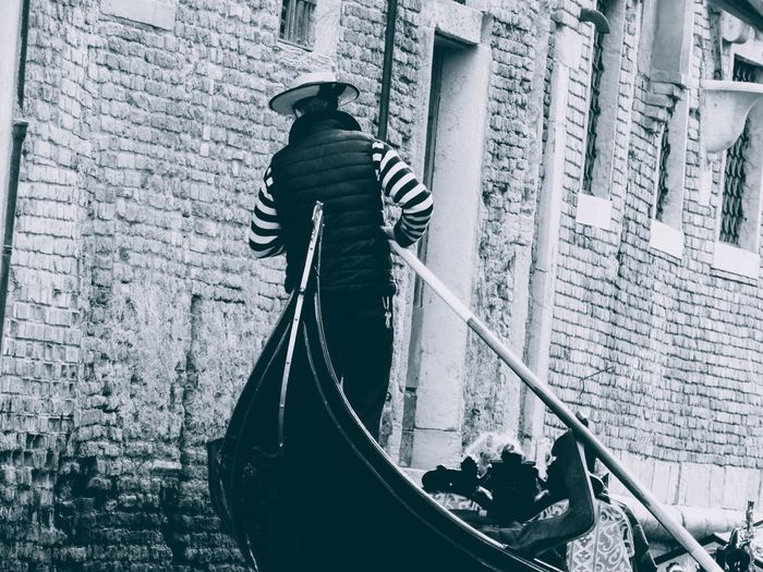Rear view of man standing on boat against building
