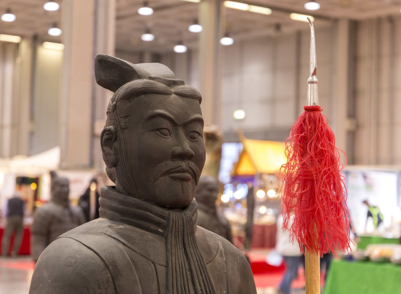 statue, focus on foreground, sculpture, indoors, hanging, no people, illuminated, close-up, day