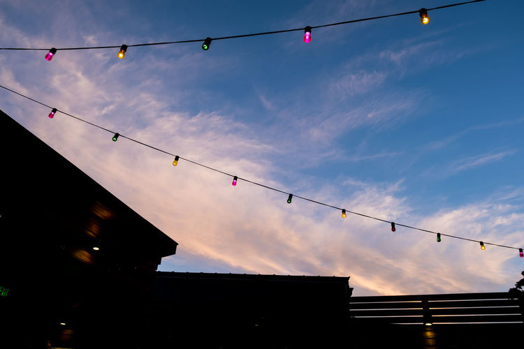 Low angle view of silhouette lanterns hanging against sky at dusk
