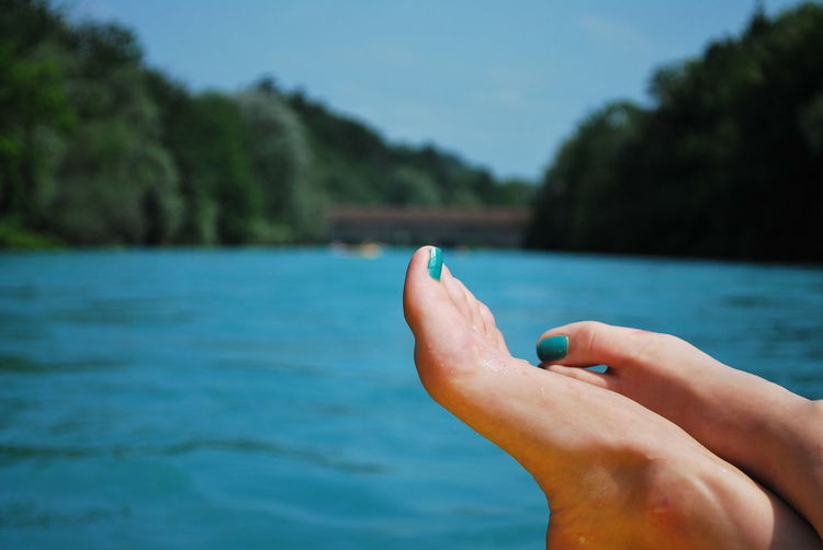 Low section of woman relaxing by lake against blue sky during sunny day