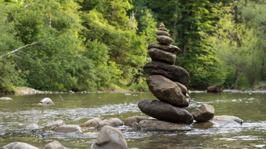 Stack of stones amidst river at forest