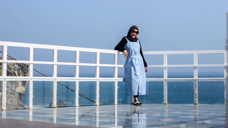 Woman standing by railing against clear blue sky