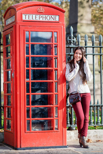 Happy tourist girl in London stands next to a classic, red telephone booth Telephone Booth One Person Full Length Telephone Young Adult Technology Smiling Adult Communication Looking At Camera Portrait Women Beauty Beautiful Woman Lifestyles Casual Clothing Outdoors Hairstyle Day Young Women London Tourist Traveler United Kingdom Classic Traditional Red Sightseeing Trip Travel Woman Tourism
