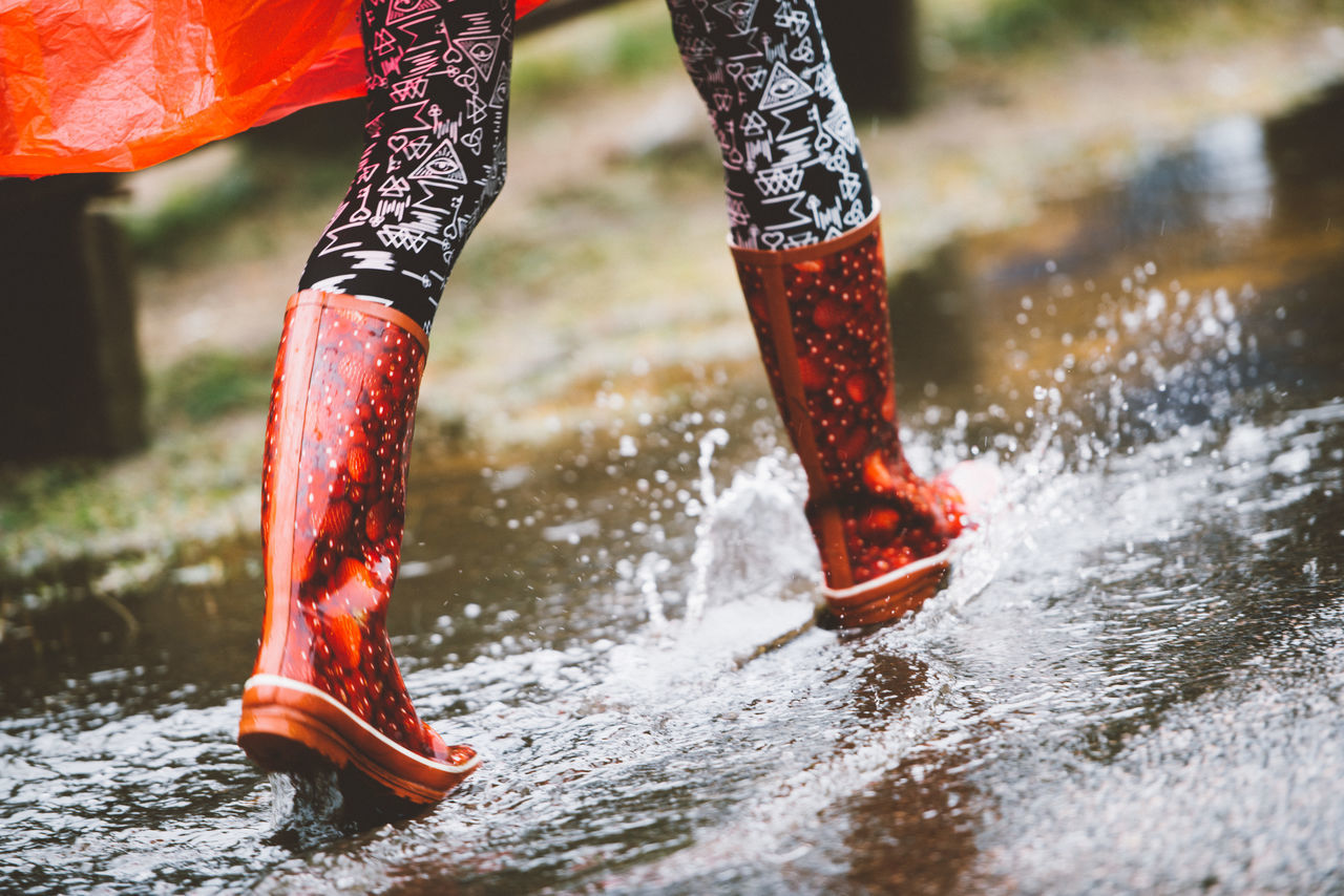Low Section Of Woman Running On Road During Rainy Season
