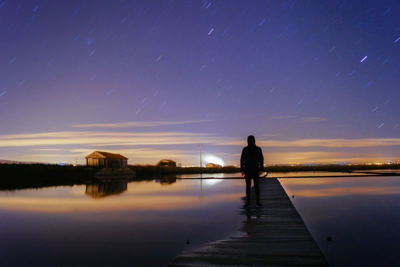 Man Standing On Jetty At Night