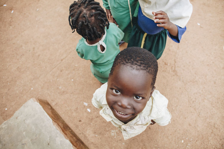 Africa African Boy Cheerful Child Childhood Children Children Only Dirt Friends Friendship Girl Ground Happiness High Angle View Kids Looking At Camera Muslim Playing Rural School Smiling Students Togetherness Uniform