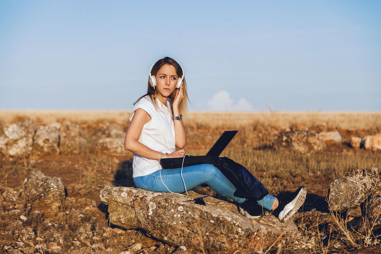 Young woman with laptop sitting on land against sky