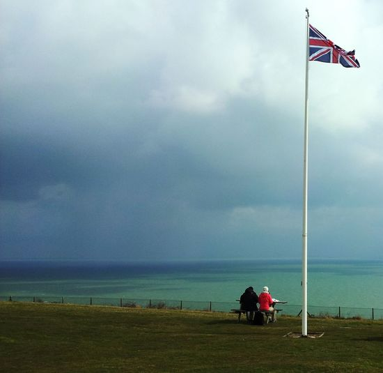 People sitting by union jack flag at beach