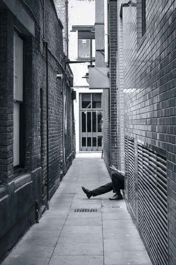 Low section of man amidst buildings at alley in city