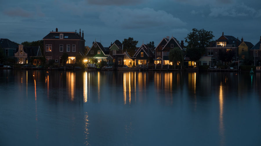 Illuminated buildings by lake against sky at dusk