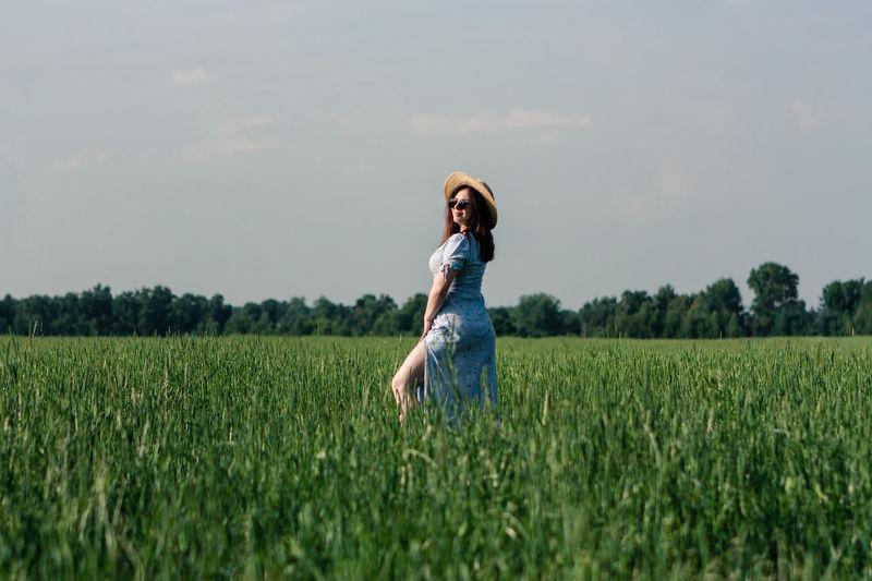 Woman in hat in the green field