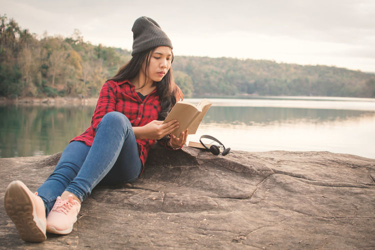 Young woman lying on rock reading book by lake against clear sky