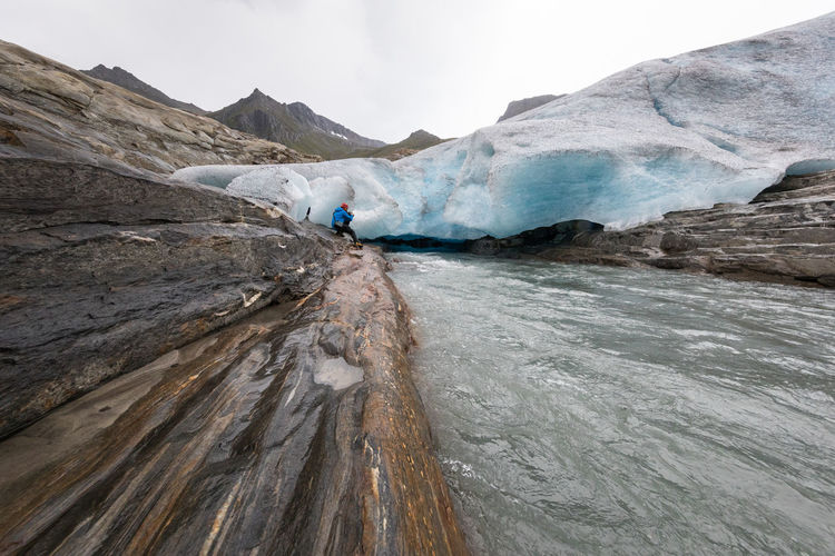 Wide angle shot of river coming out of a glacier and a man sitting in front of it (Engabreen, Svartisen) Ice Svartisen Activity Adult Adventure Arctic Beauty In Nature Challenge Climate Change Cold Temperature Extreme Sports Extreme Terrain Glacier Hiking Landscape Men Motion Mountain Nature One Man Only Polar Climate Real People RISK River Rock - Object Lost In The Landscape