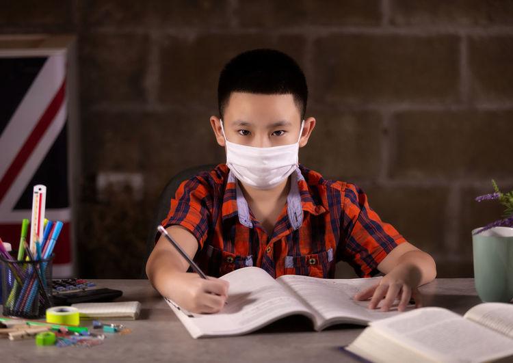Portrait of boy reading book