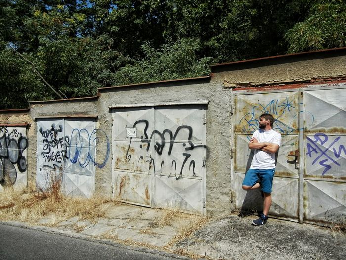 Man with arms crossed leaning against graffiti wall