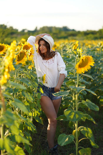 Portrait of young woman standing in sunflower field