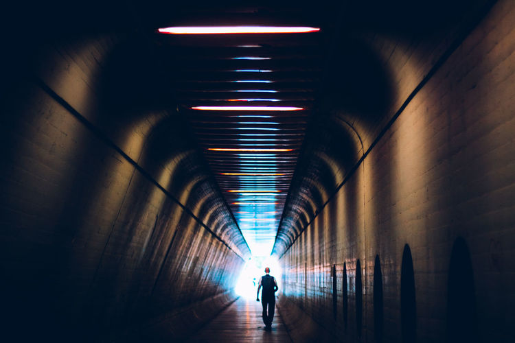 Silhouette man walking in illuminated tunnel
