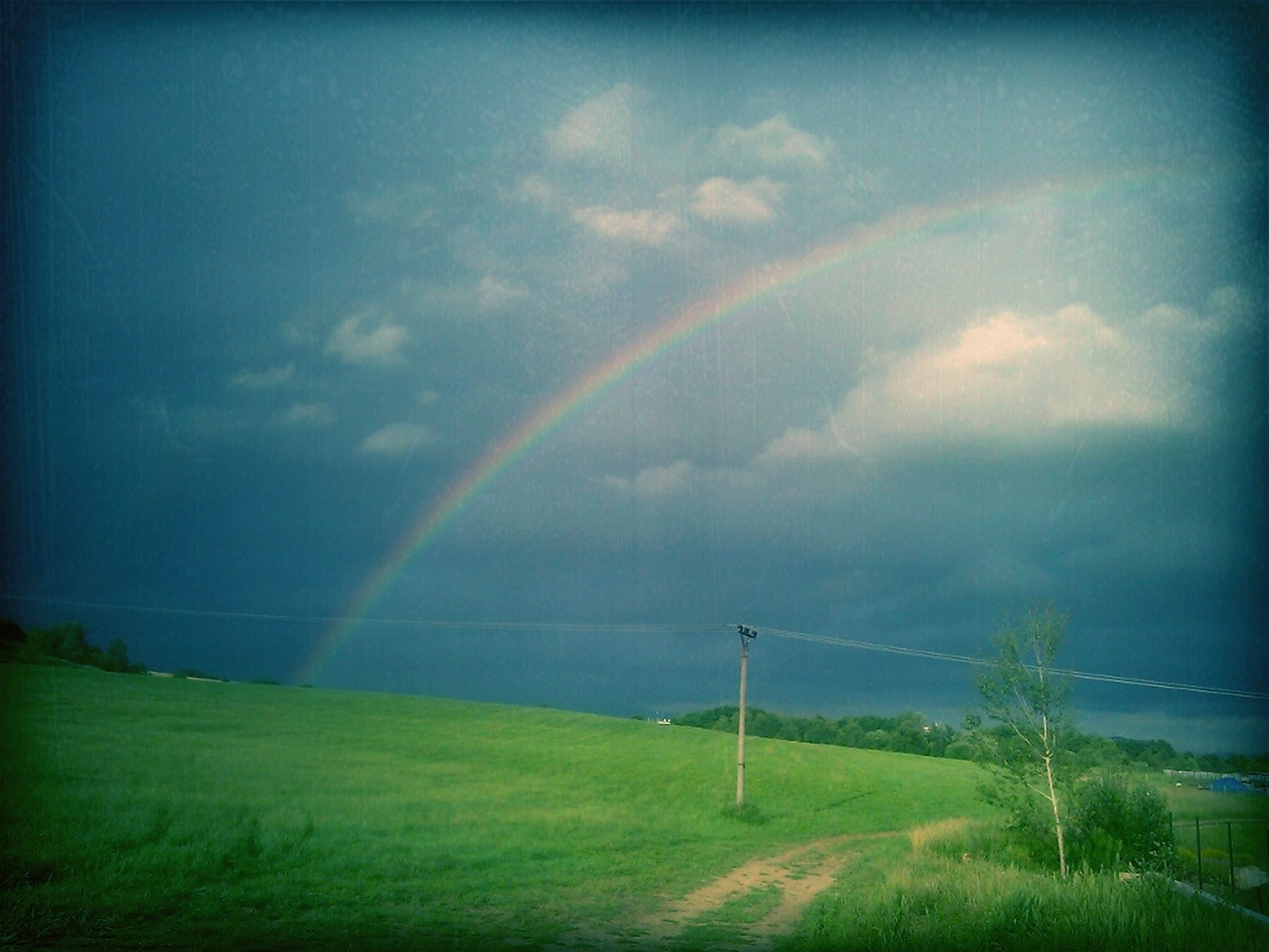 landscape, sky, rainbow, tranquility, tranquil scene, scenics, field, beauty in nature, grass, cloud - sky, nature, weather, cloudy, idyllic, rural scene, grassy, green color, cloud, non-urban scene, storm cloud