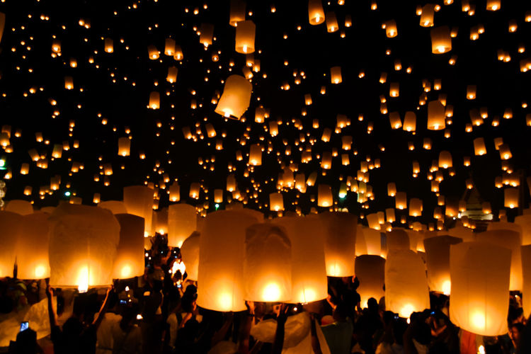 Group of people with illuminated paper lanterns at night