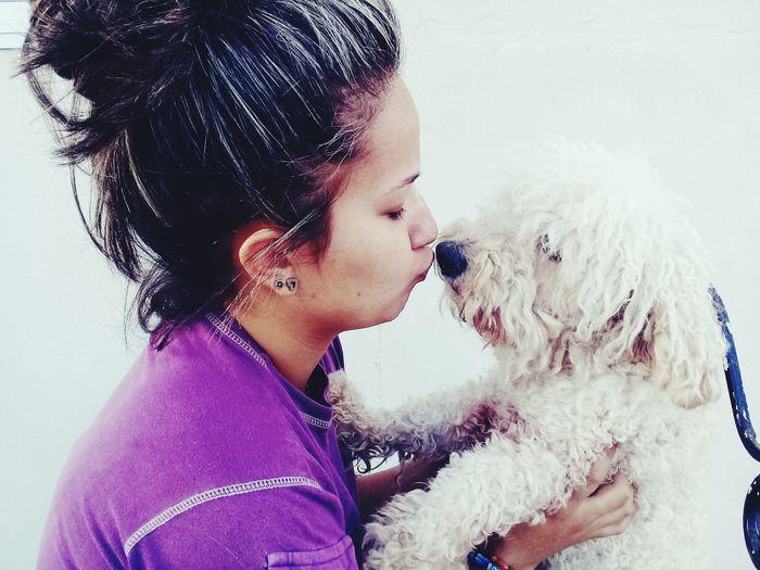 Woman Kissing Dog At Home