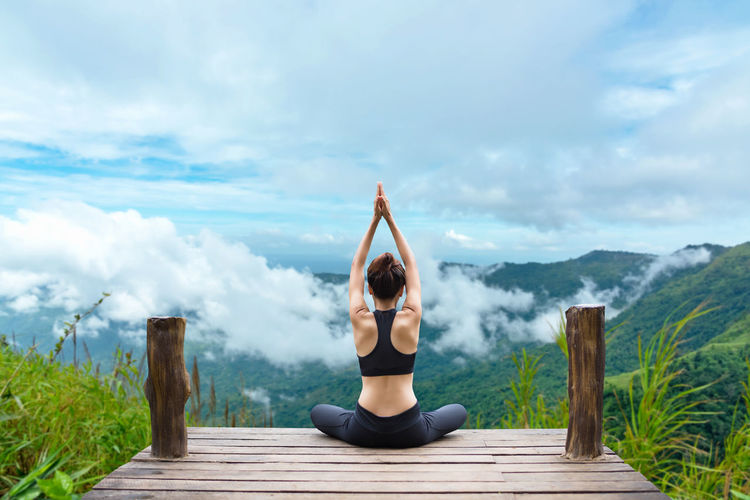 Full length of woman relaxing on mountain against sky