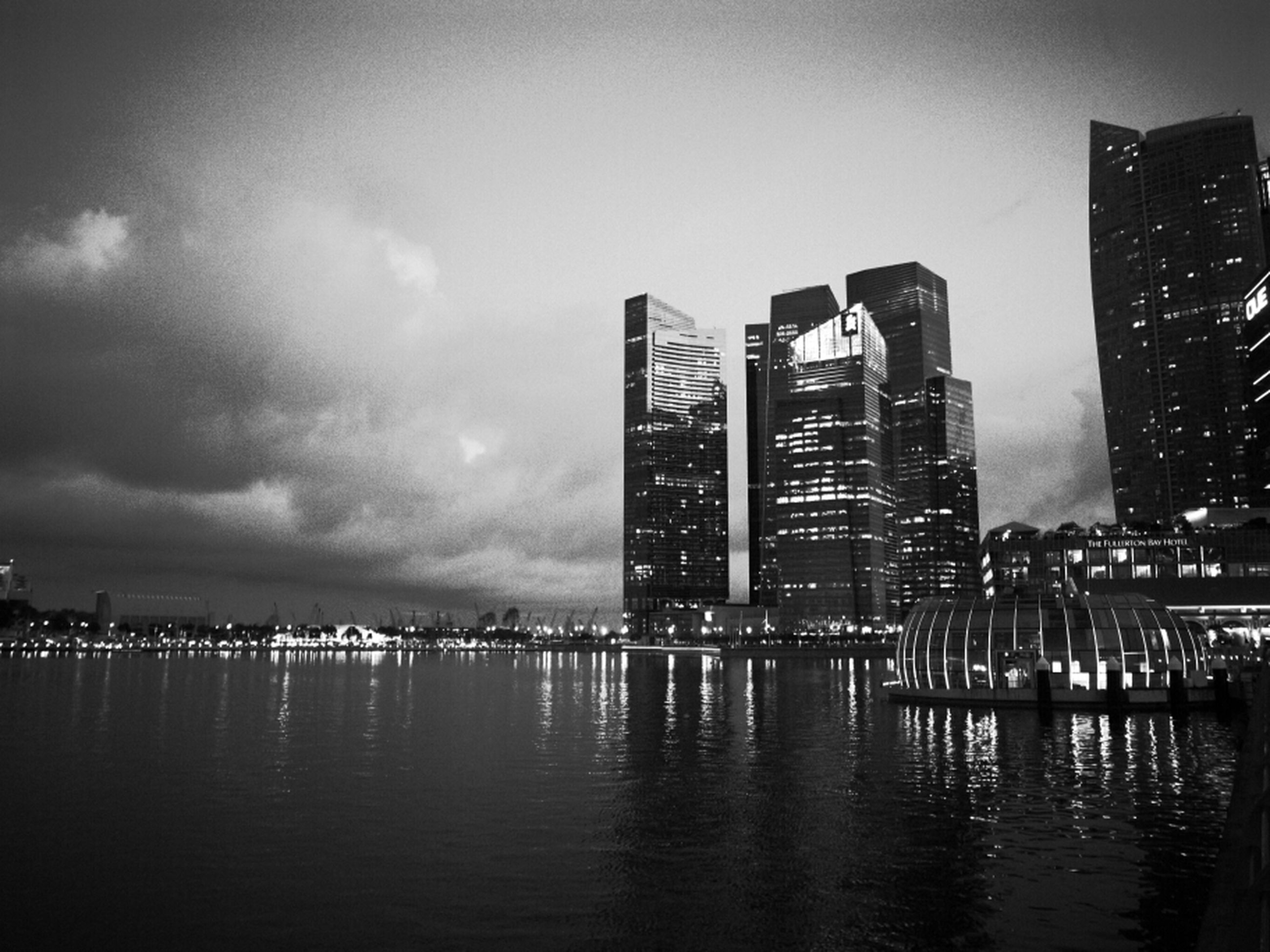 water, building exterior, architecture, built structure, waterfront, sky, city, illuminated, reflection, skyscraper, night, sea, river, dusk, cloud - sky, cityscape, urban skyline, tall - high, tower, modern