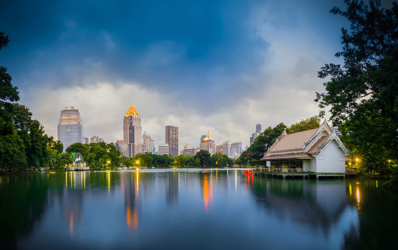 Reflection of buildings in lake against cloudy sky
