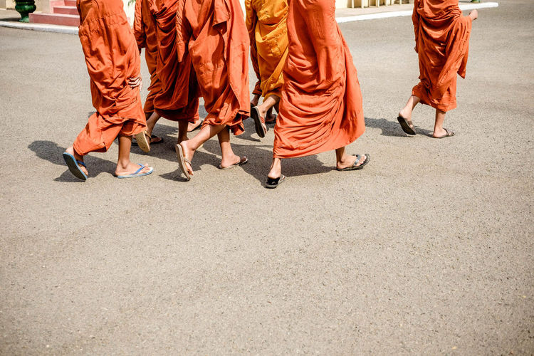 Low section of monks walking on road