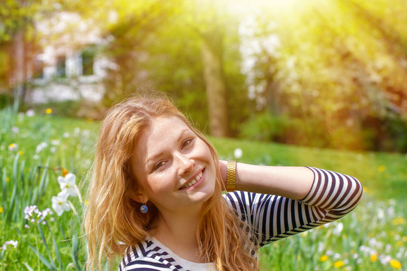 Young, happy woman in the sun Smiling Happiness Portrait Emotion Women Hairstyle Long Hair Nature Cheerful Leisure Activity Lifestyles Sunlight Beauty Outdoors Hair Girl Spring Sun Healthy Eating Relax Relaxation Young Women Red Hair Season  Meadow