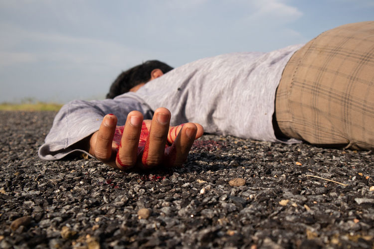 Close-up of man lying down on road against sky