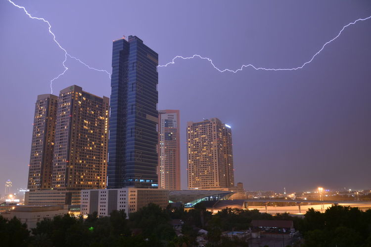 Low Angle View Of Buildings Against Sky In City During Lightning