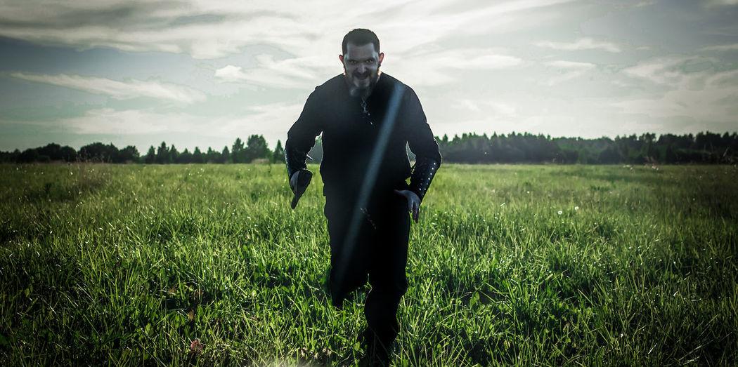 Man running on field against sky