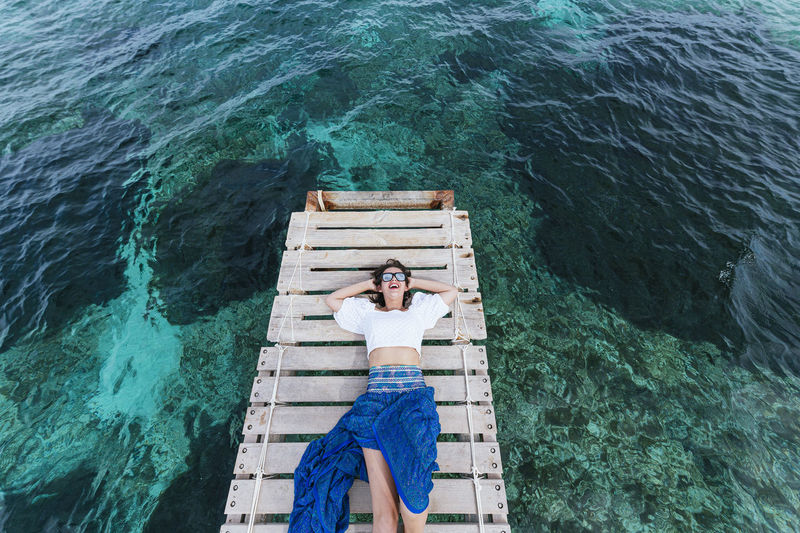 High angle view of man relaxing by sea