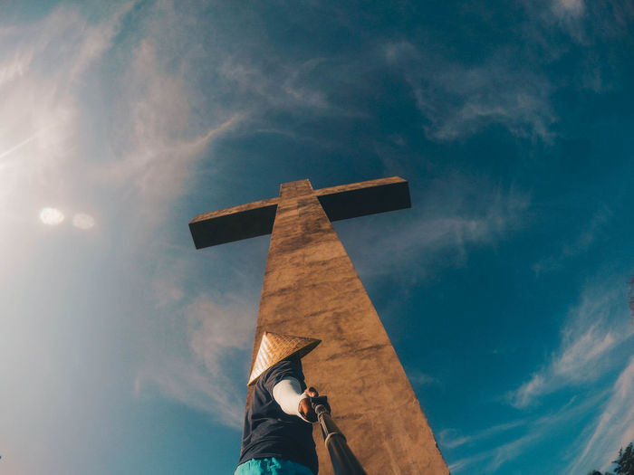 Low angle view of man standing by tall cross against sky