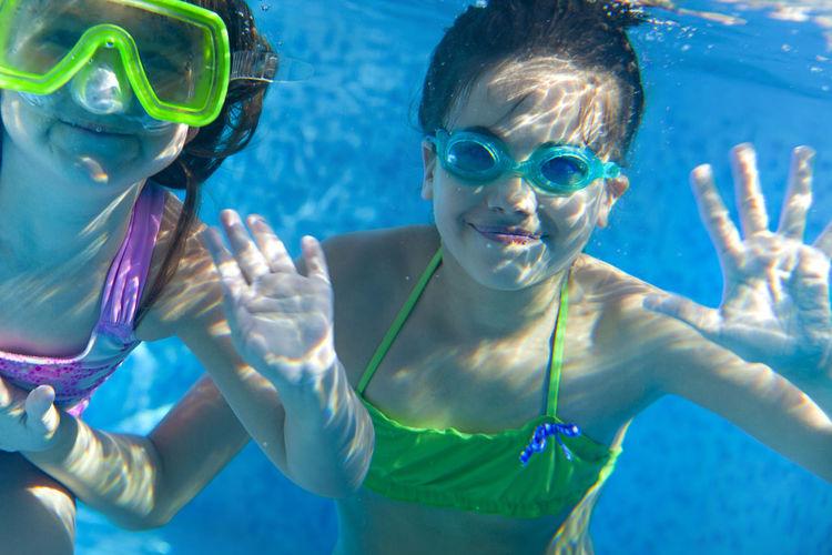 Portrait of sisters underwater in swimming pool