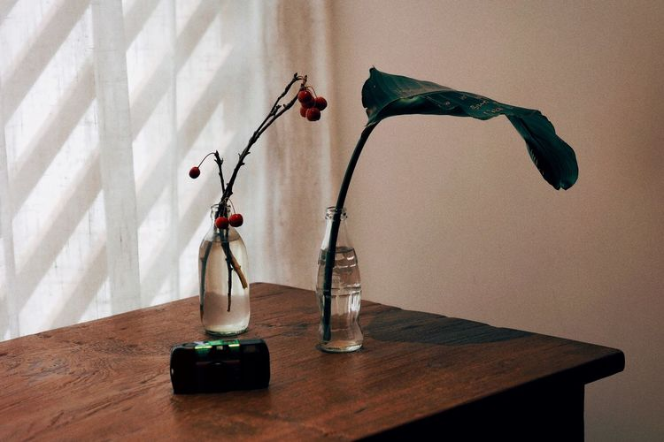 Red rose in vase on table against wall at home