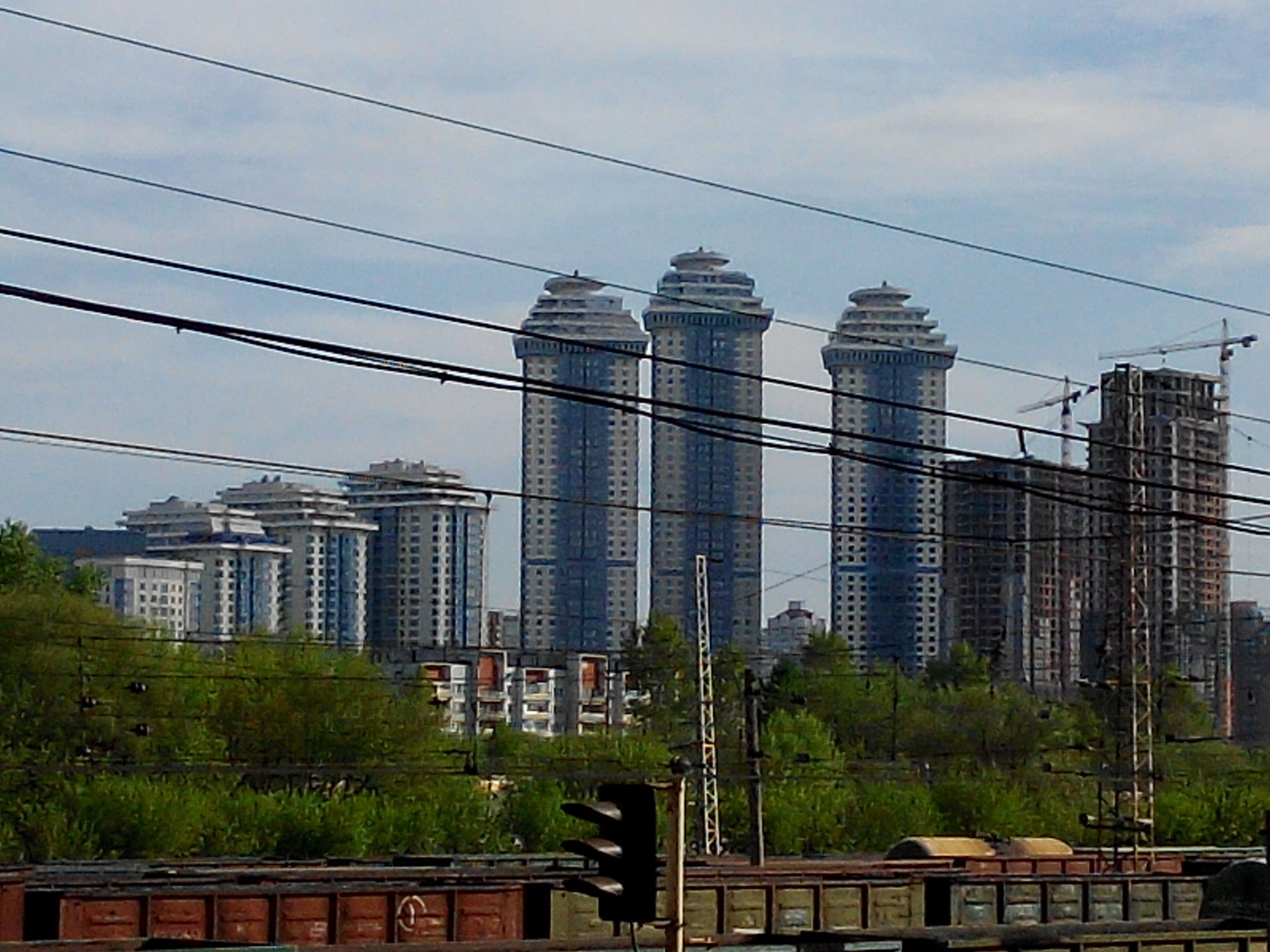 building exterior, architecture, built structure, city, skyscraper, office building, modern, sky, tower, tall - high, glass - material, tree, building, city life, day, low angle view, growth, cloud - sky, cityscape, no people