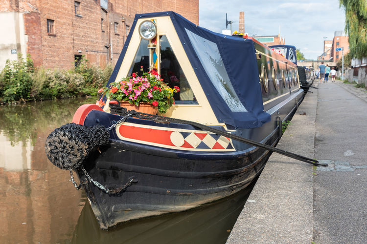 Barge moored in city canal Barge Colourful Architecture Boat Building Exterior Built Structure Canal City Day Flower Flower Pot Flowering Plant Focus On Foreground Incidental People Mode Of Transportation Moored Nature Nautical Vessel Outdoors Plant Potted Plant Street Sunlight Transportation Water