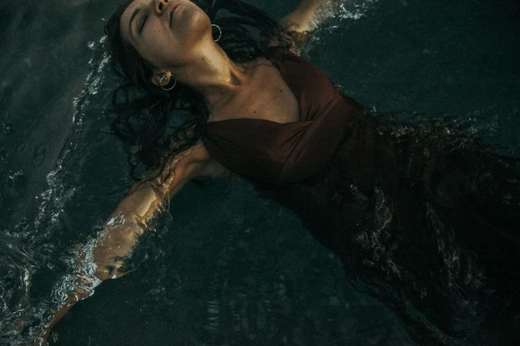 High angle view of woman lying in swimming pool